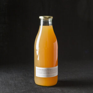 Birnensaft mit frische grünen Wacholderbeeren in Glasflasche